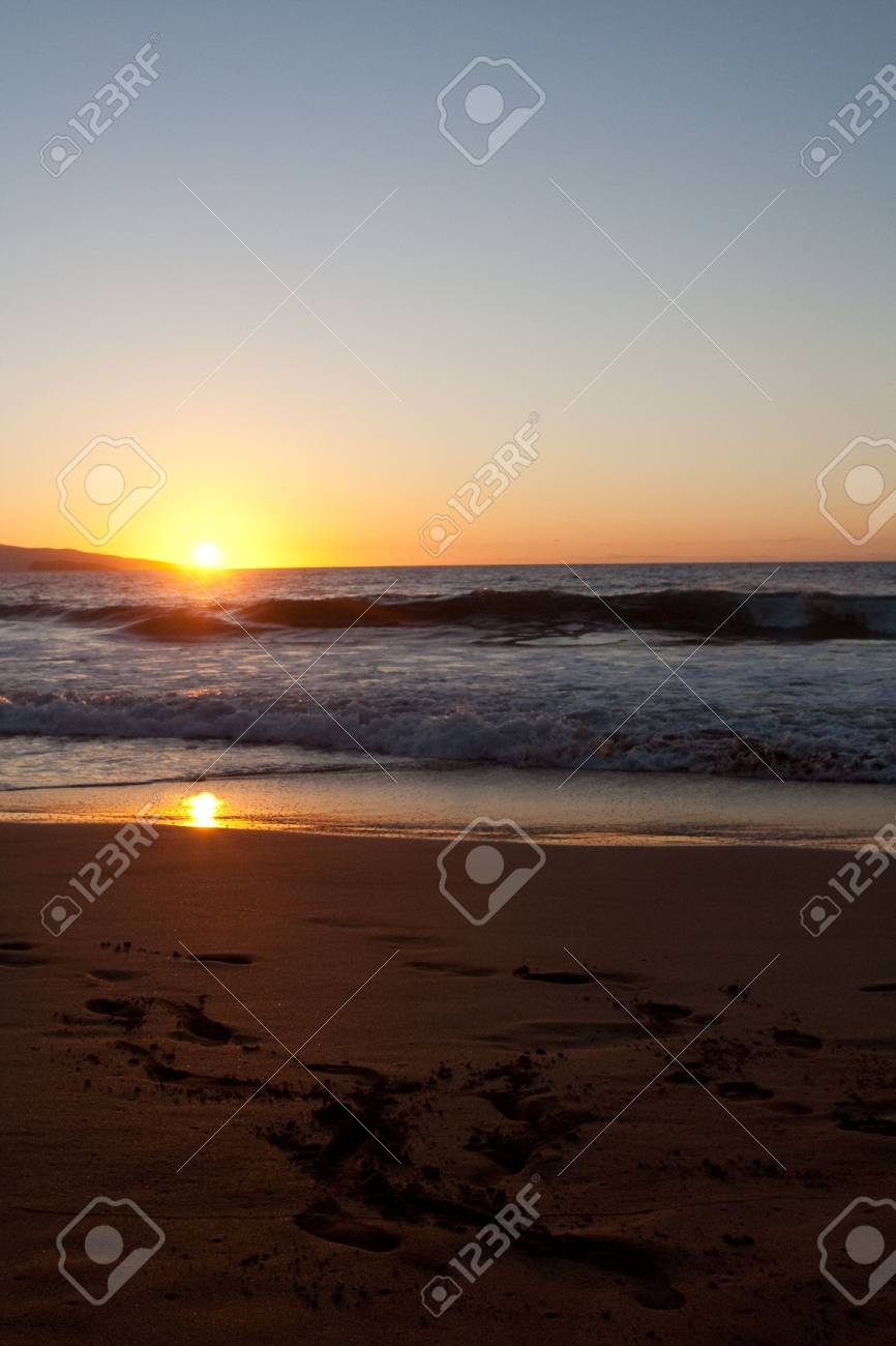 Sunset on the beach with foot prints in the sand and waves Stock Photo - 6361393