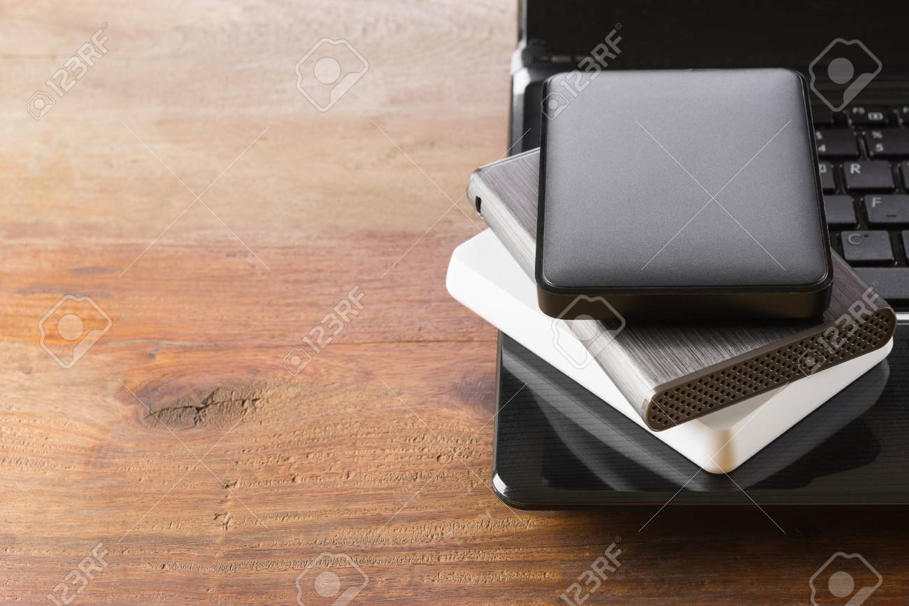 stack of portable external hard drive on laptop computer with