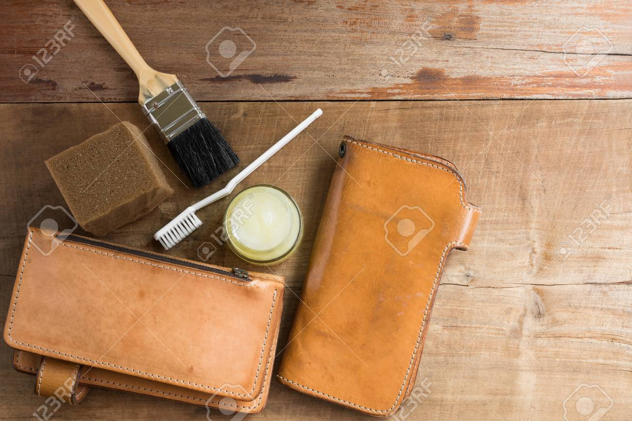Stock Photo - top view of old genuine leather wallet on wooden table  prepare to clean and care with wax. maintenance concept. 58139ea914bc