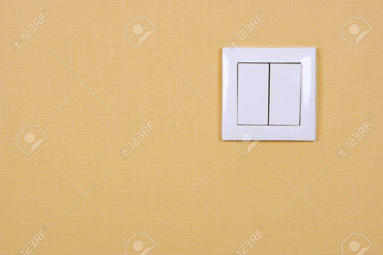 Wall-mounted electric switch in white on a yellow wall Stock Photo - 9027548
