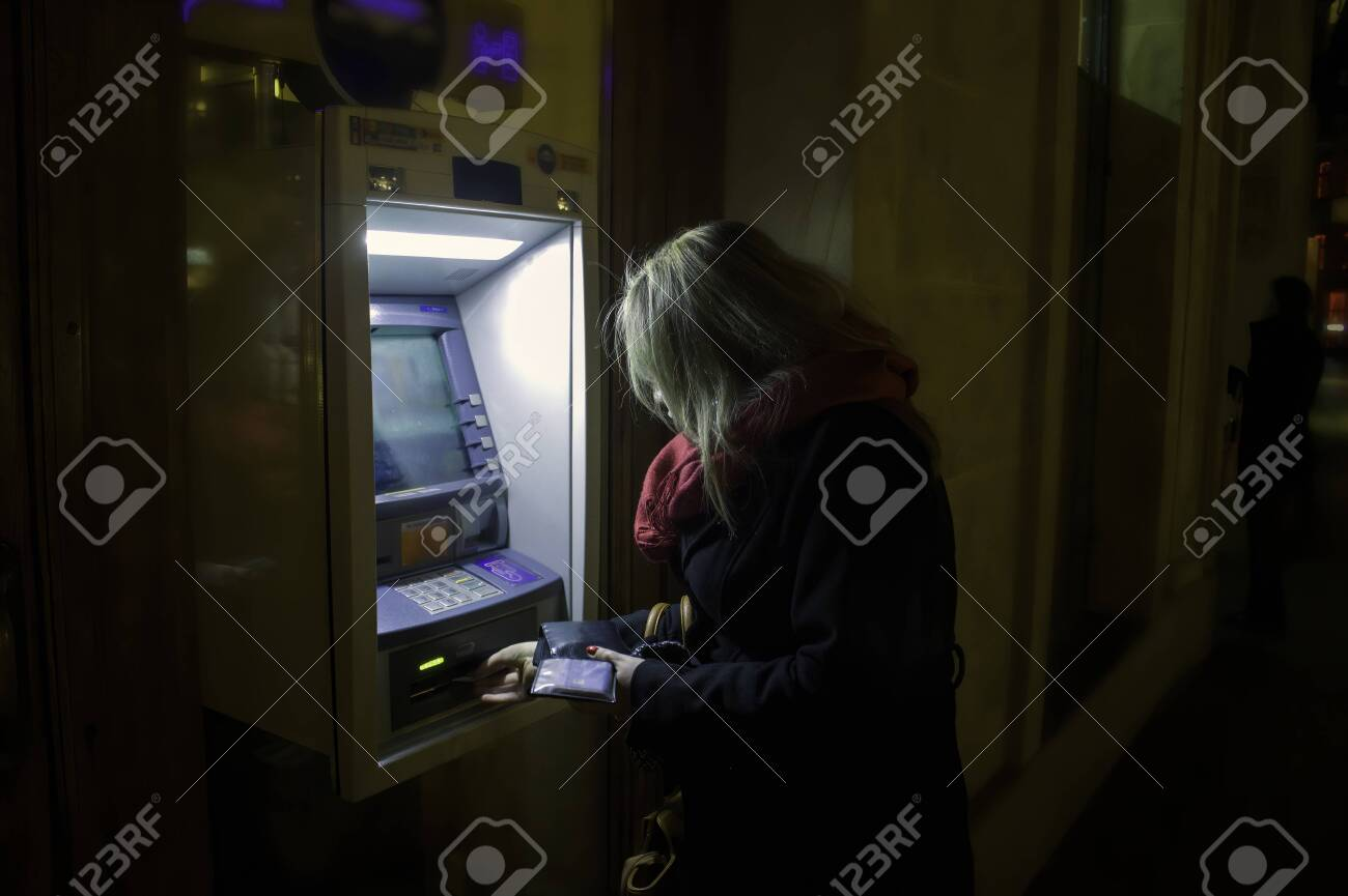 Krakow, Poland - October 25, 2014: A woman using ATM at night in winter - 151823484