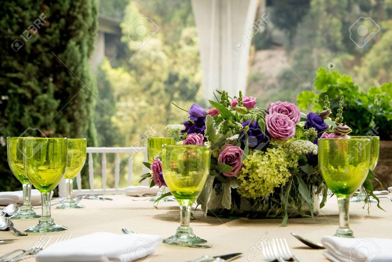 Formelle Tisch Einstellung Für Eine Hochzeit Mit Floralen Herzstück Und  Bunte Grüne Gläser Vor Einem