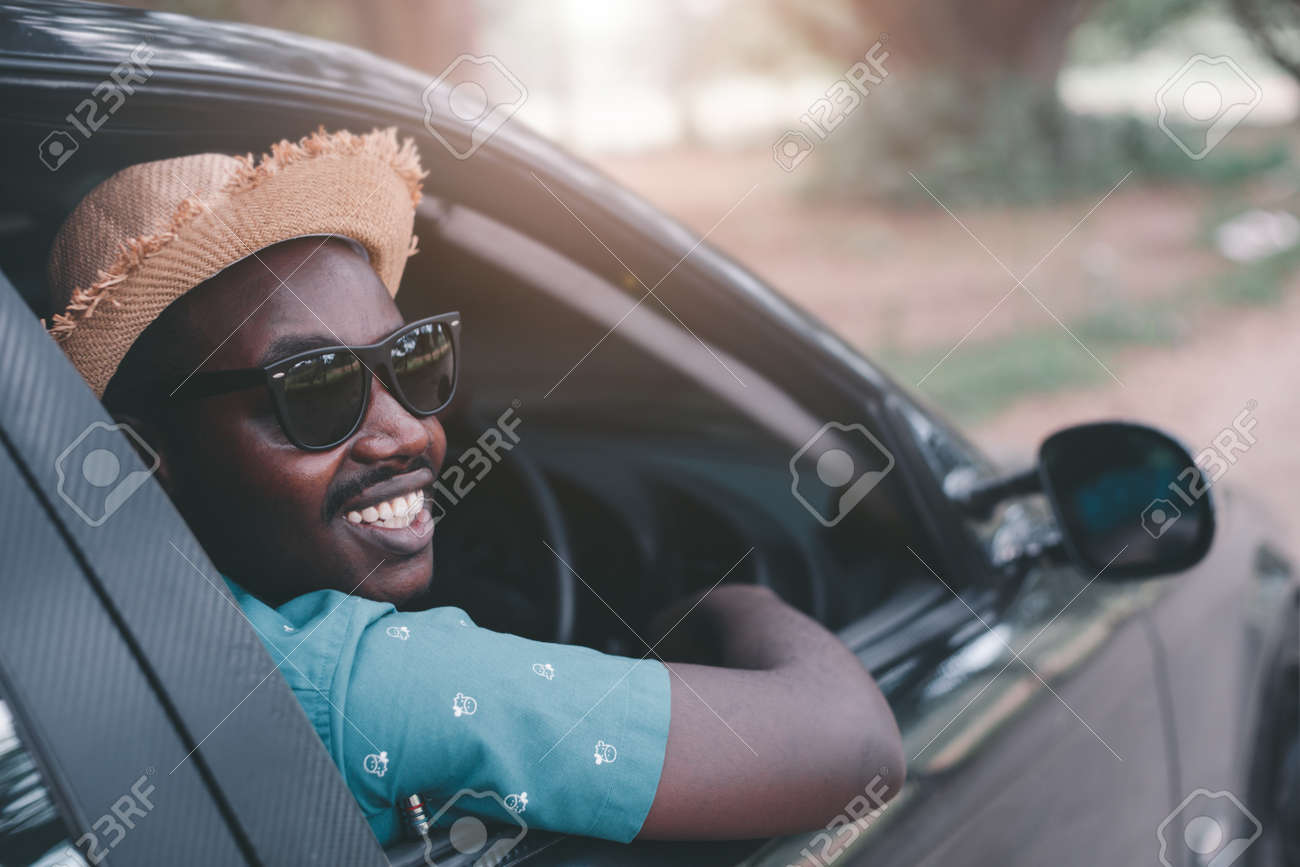 Happy african driver smiling while sitting in a car with open front window - 165592764