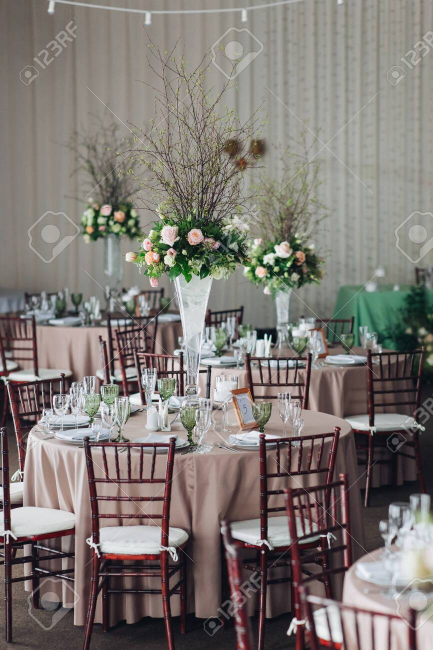 Beautiful composition with flowers on the tables and candles for guests at a wedding or a birthday party. - 128843698