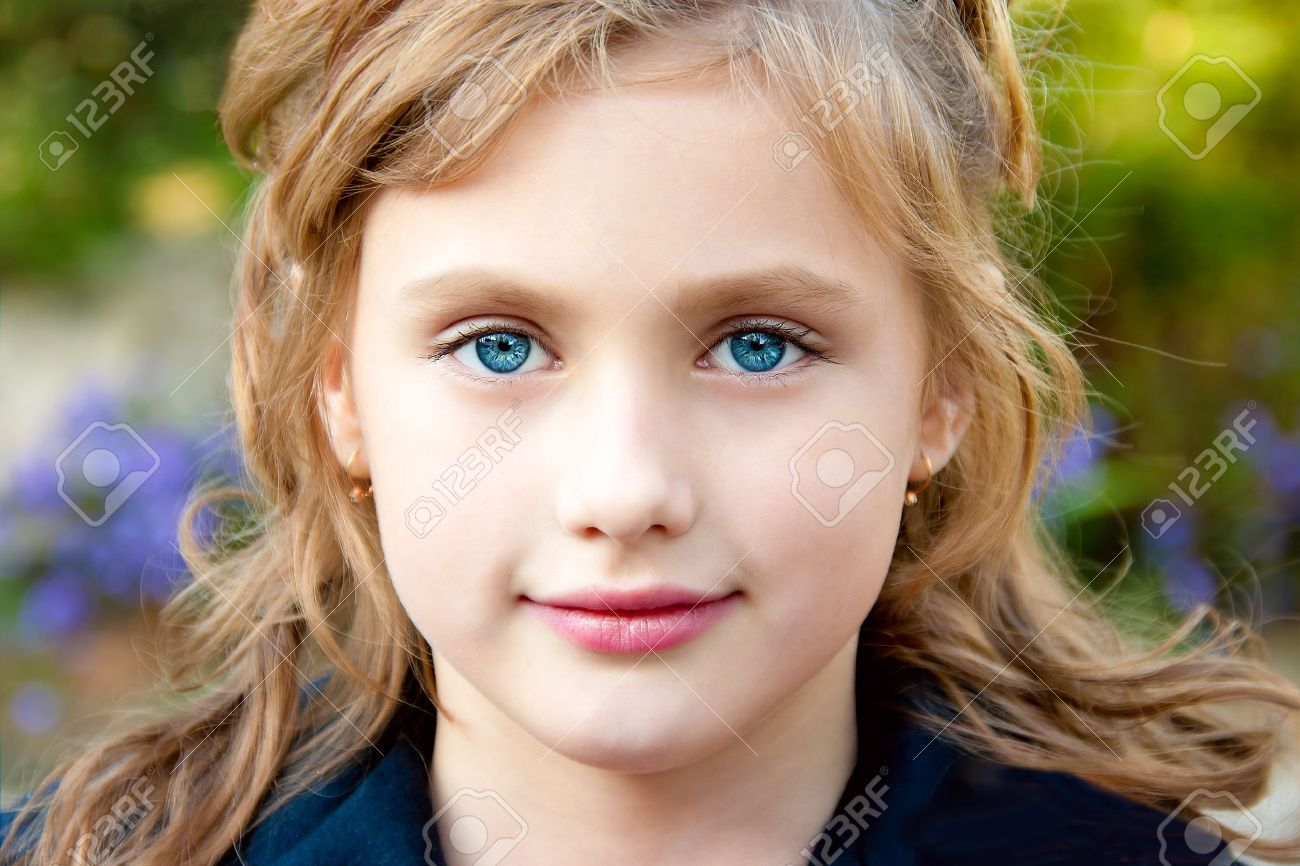 600356127e0 Portrait of a pretty little girl on the background of nature. Stock Photo -  9666224