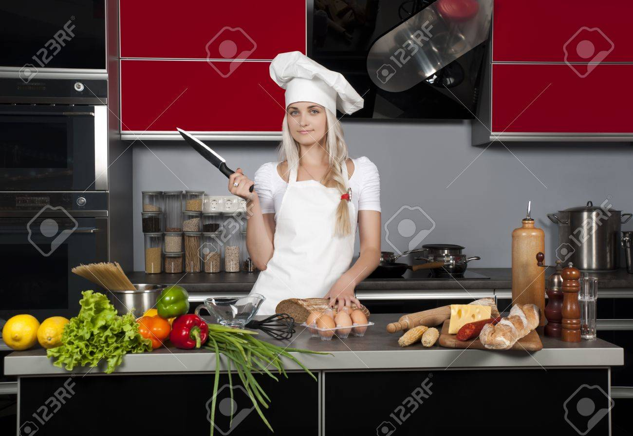 young beautiful chef in the kitchen with a knife in hand
