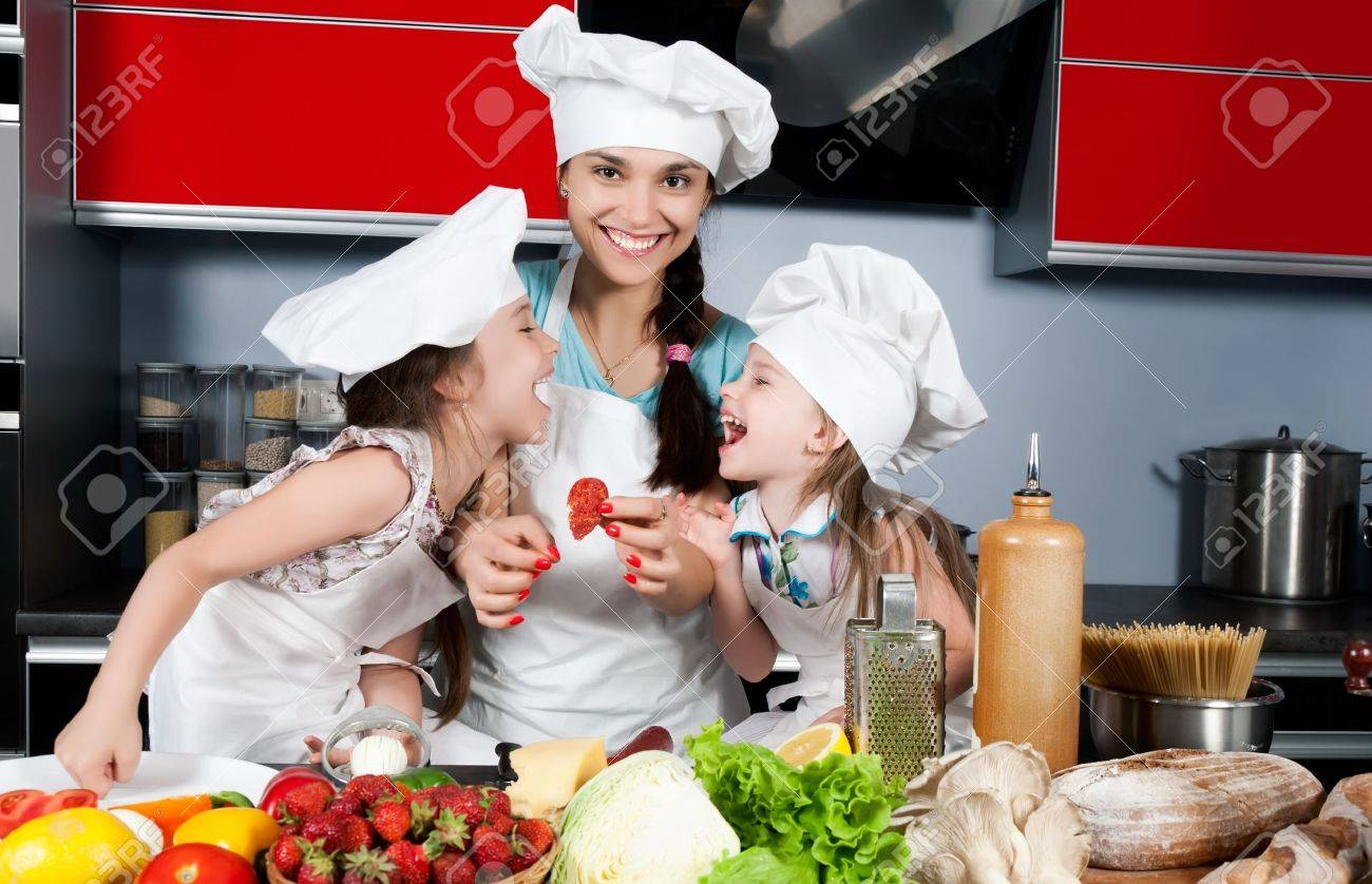 Mom teaches two daughters to cook at the kitchen table with raw food, clothing cooks Stock Photo - 9808717