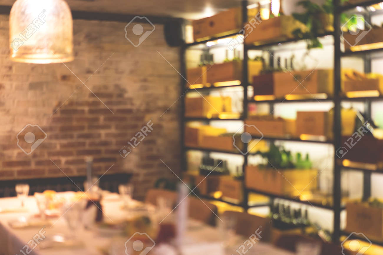 Blurred cafe background with served festive table and beautiful lighting of wine racks. - 122200781