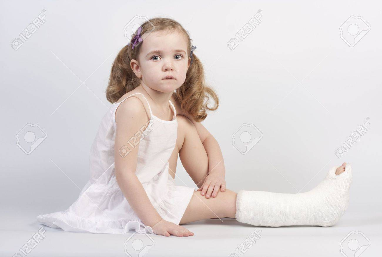 Little girl injured with broken ankle sitting on white backgound. Stock Photo - 6545995