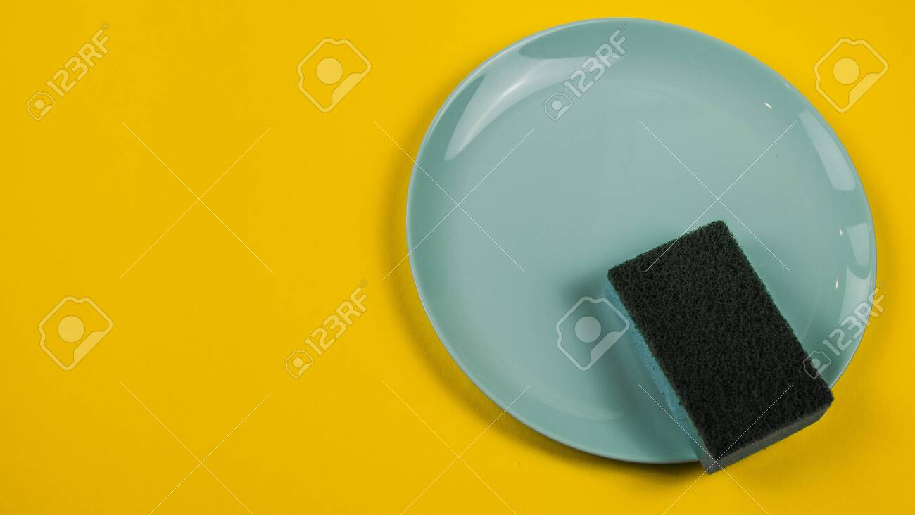 Cleaning sponge on a green plate on an orange background. - 142343716
