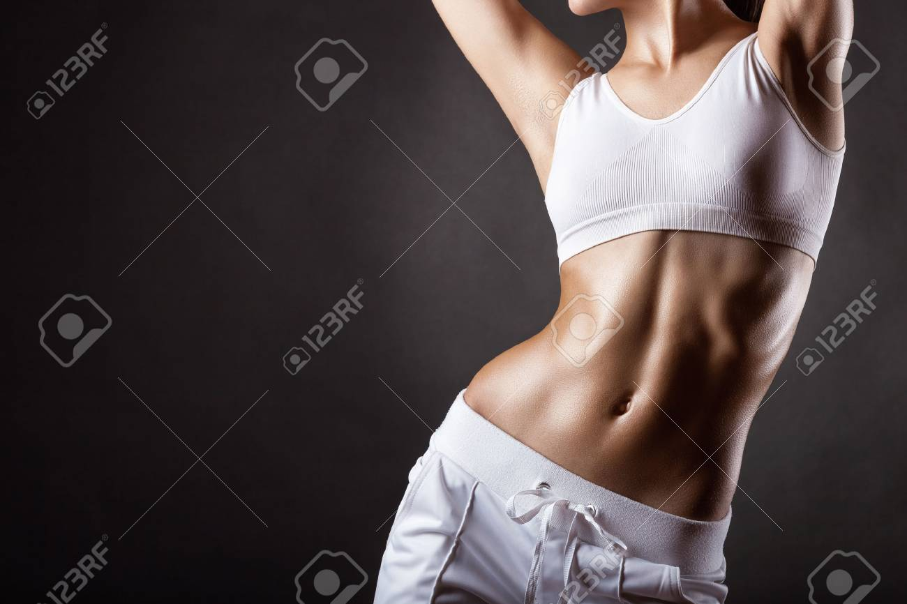 The body of a young athletic girl on a dark background - 35453327