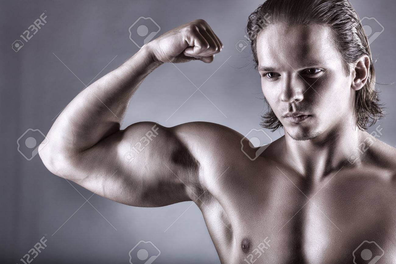 Portrait Of Man With Muscular Arms On A Gray Background Stock Photo