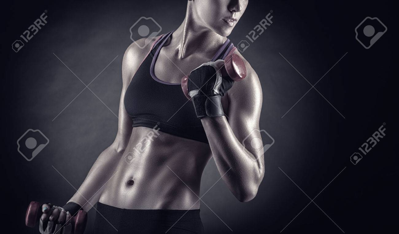 Fitness girl with dumbbells on a dark background - 38380282