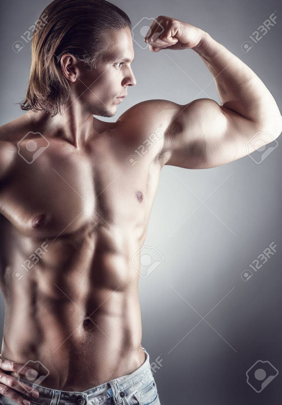 Portrait Of Man With Muscular Arms On A Grey Background Stock Photo