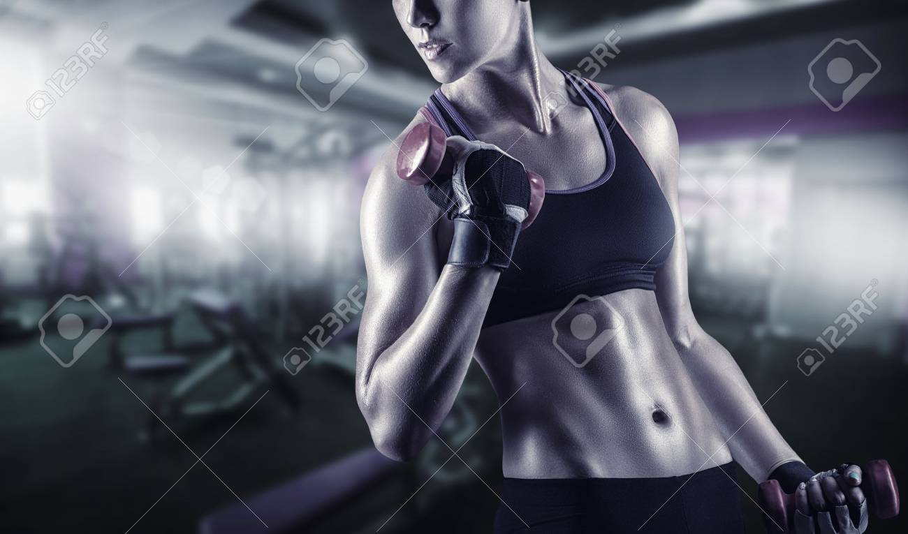Close-up of a young woman exercising with weights in the gym - 61084364