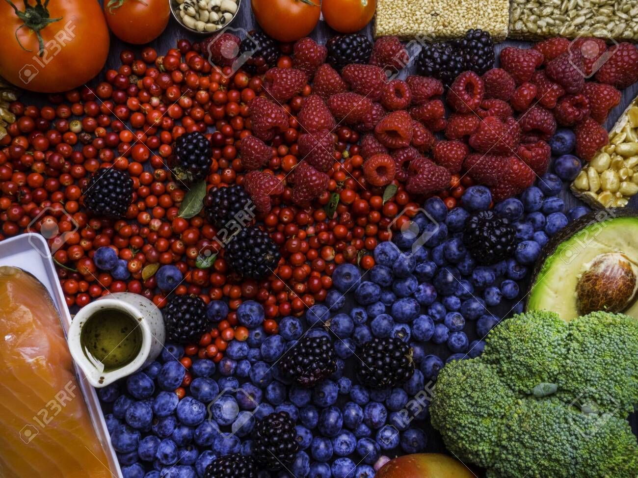 Clean eating concept over wooden background, top view. Variety of vegetables, fruit, seeds, bean, superfood, salmon fish, condiment for vegan, raw diet or gluten free diet, food for heart - 129190612
