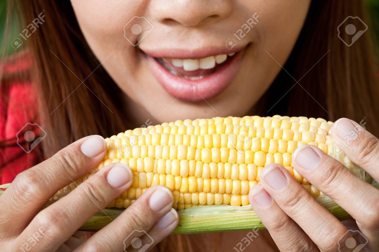 Young woman going to eat fresh yellow corn Stock Photo - 13382409