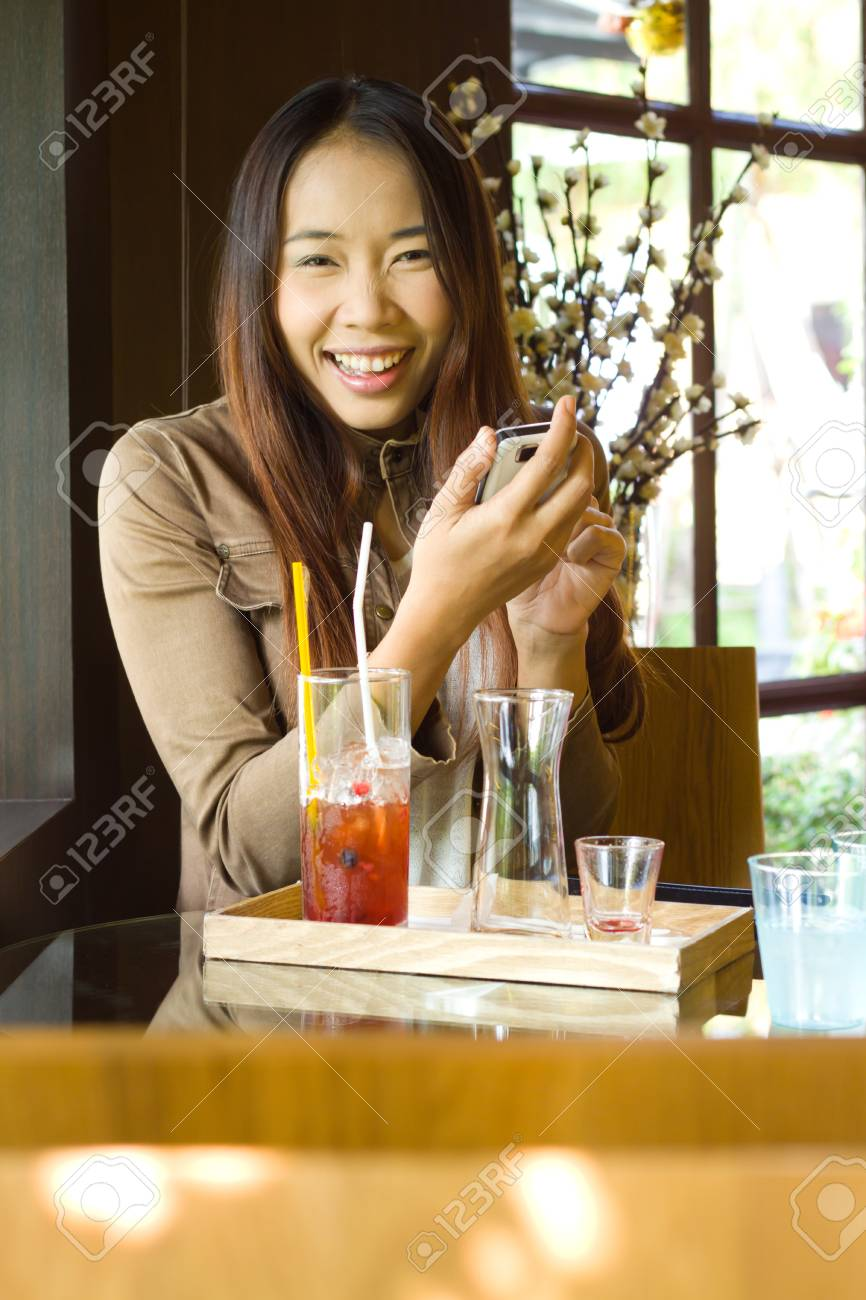 Young happy asian woman texting message in the restaurant Stock Photo - 19060496
