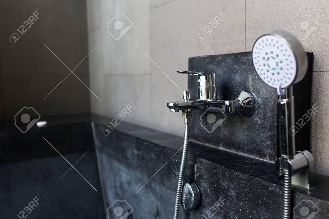 Jacuzzi moderne avec robinet et douche à main dans une salle de ...