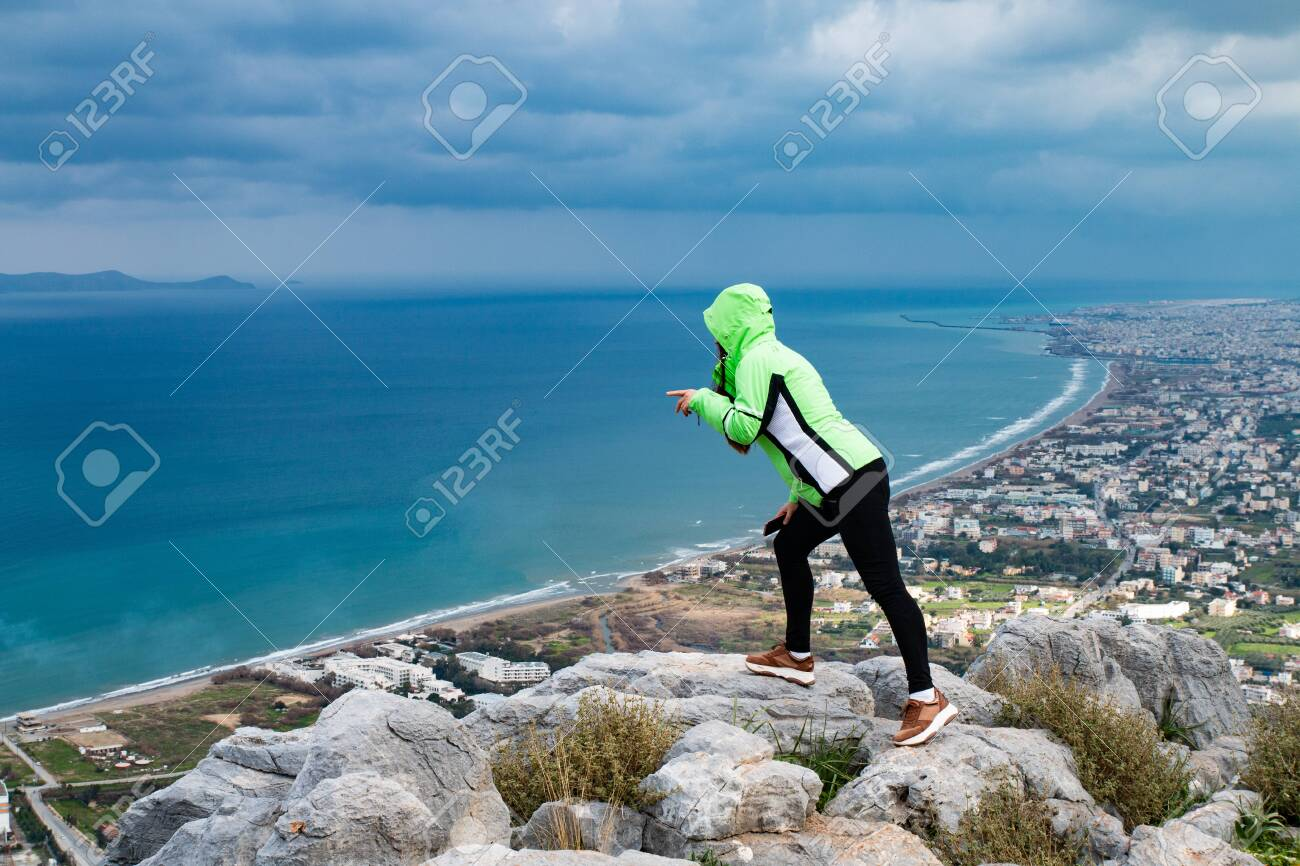 A young woman standing on a mountain and looking down. A girl stands and looks at the sea. A girl stands on a high mountain in the background of the city and the sea. - 142962670