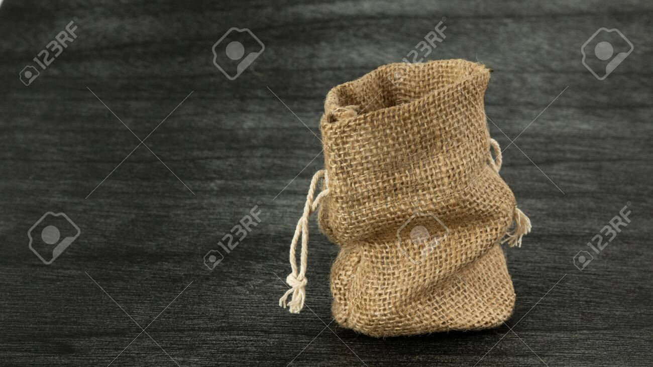 Burlap sack on dark background. Jute Empty Sack mock up. Copy space for text. Traditional Vintage Sack mock up. Linen sack copy space for product. - 145516855