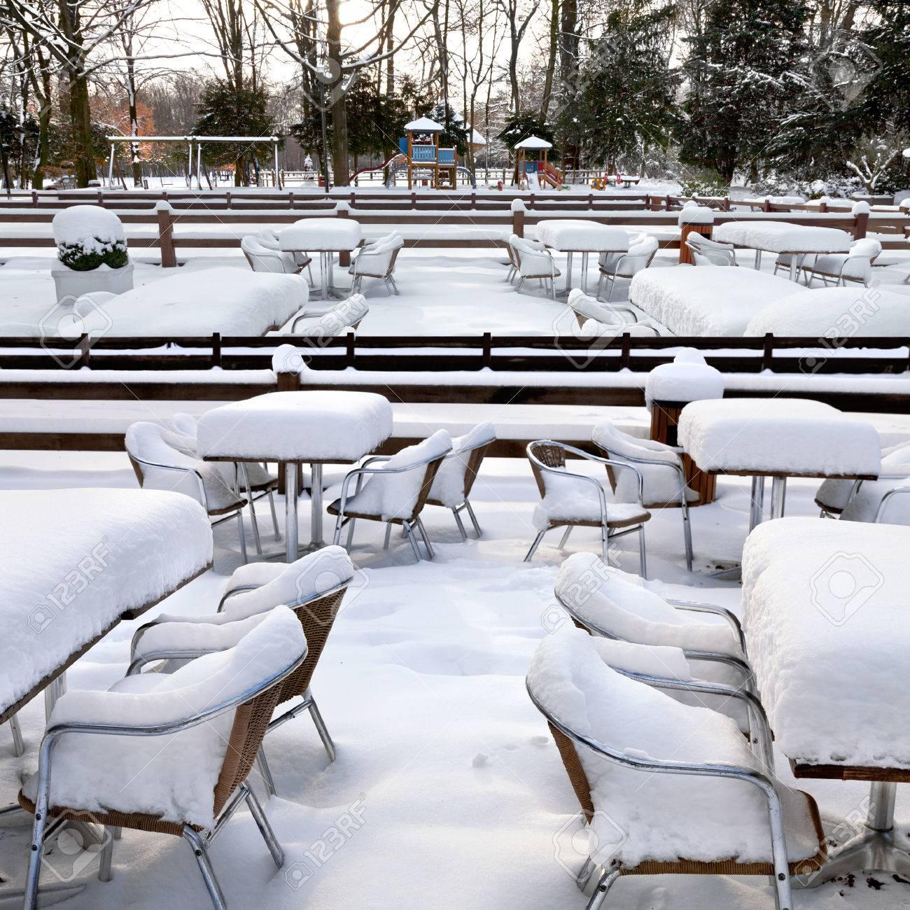 cafe with snow winter landscaper garden furniture melting after