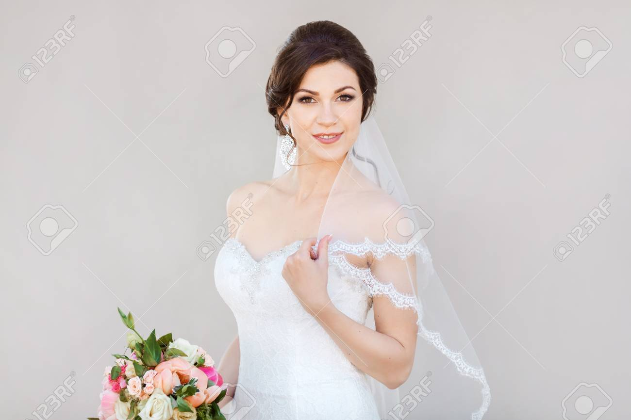 Beautiful Bride In White Wedding Dress With Bouquet Of Flowers