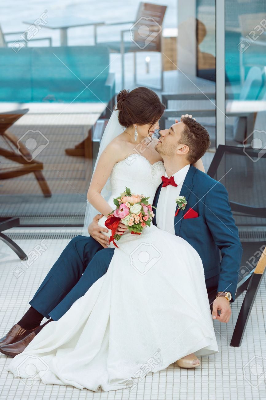 5935adf54 Wedding couple in love. Beautiful bride in white dress and veil and brides  bouquet with handsome groom in blue suit sitting on plank bed and embracing  each ...