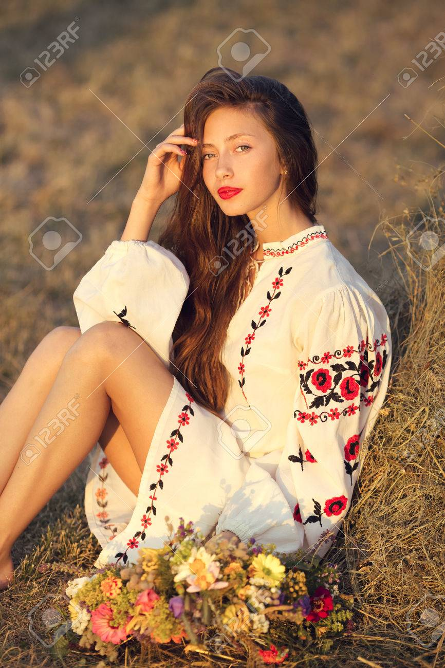 Slav teen girl at yellow meadow sitting in national ukrainian clothing with  wreath of flowers.