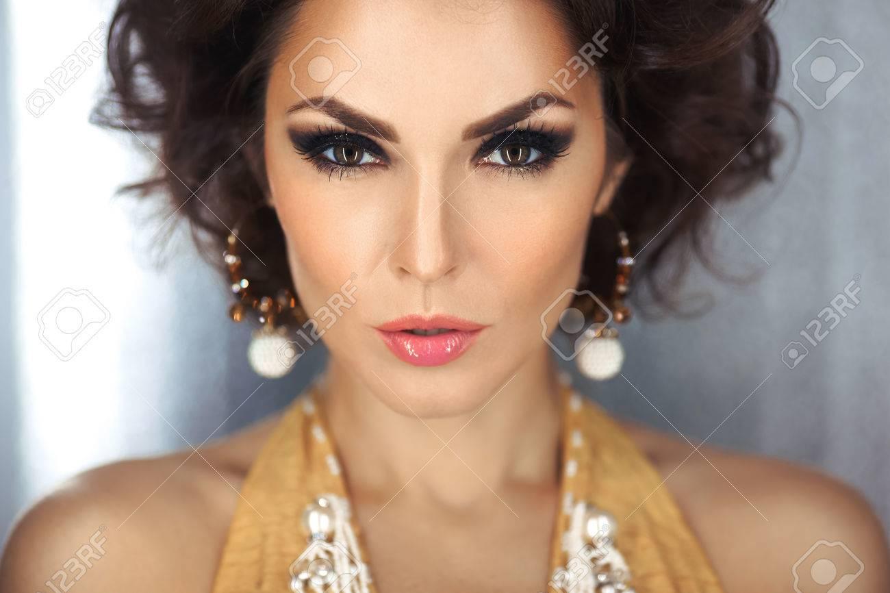 479a515a6 Mujer Hermosa Con Maquillaje De La Tarde Y El Cabello Rizado Y Vestido  Amarillo Con Perlas De Joyería. Ojos Humeantes. Moda Retrato De La Foto.