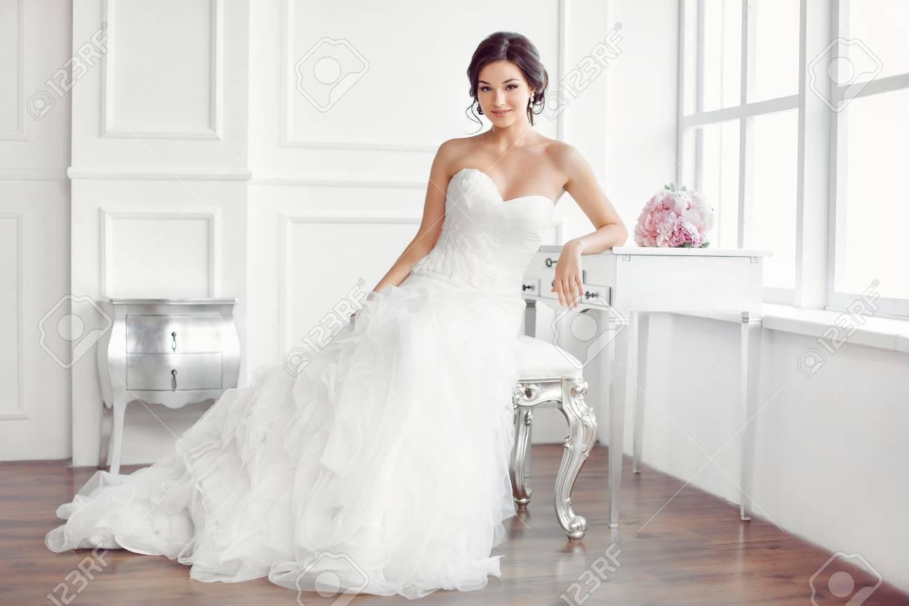 Preparación De La Boda Hermosa Joven Novia En Vestido De Novia Blanco En El Interior Luxuty Modelo Sentado En La Silla Con El Ramo De Novias Como En
