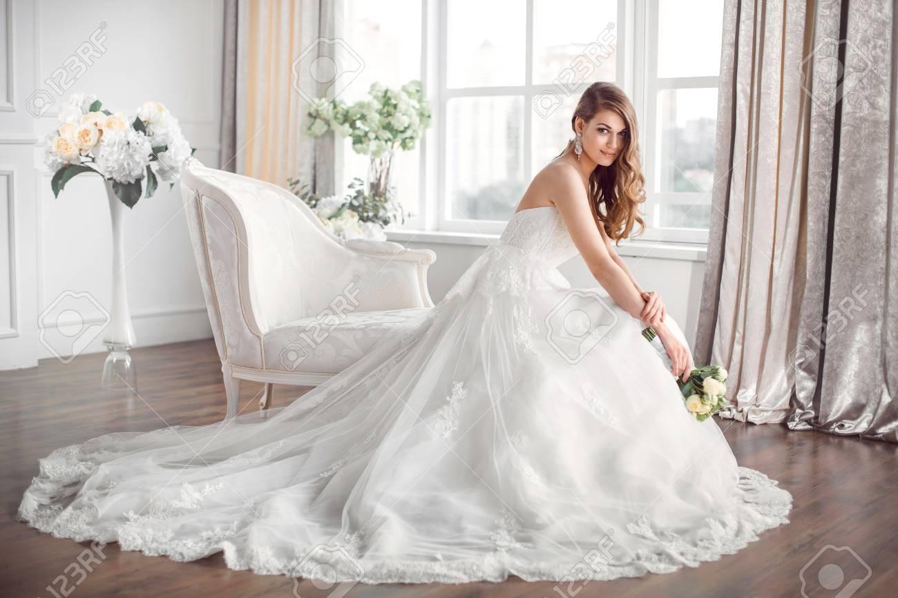 結婚式。自宅のような白いスタジオ  インテリアの室内でソファーに座っている美しいドレスの花嫁。流行の結婚式のスタイルは、完全な長さで撮影。大きな窓に花嫁のような若い魅力的な白人ブルネット  モデルは、ポーズを入札します。