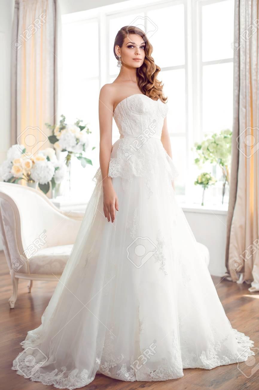 brautmode braut. perfekte hochzeit weißes kleid make-up und frisur.  wunderschöne brünette model posiert drinnen