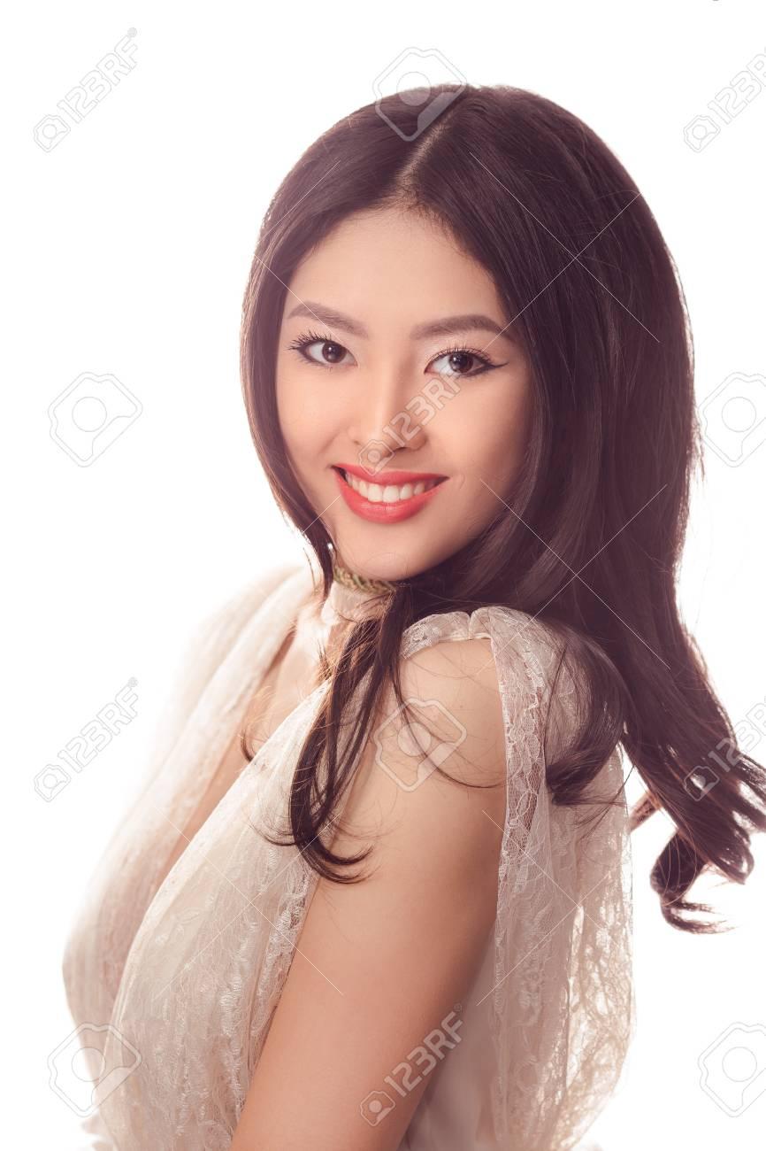 ... donna asiatica con capelli ricci lunghi che sorride sulla priorità  bassa bianca. Ritratto del primo piano della ragazza splendida in vestito  di pizzo ... 75e33313b85