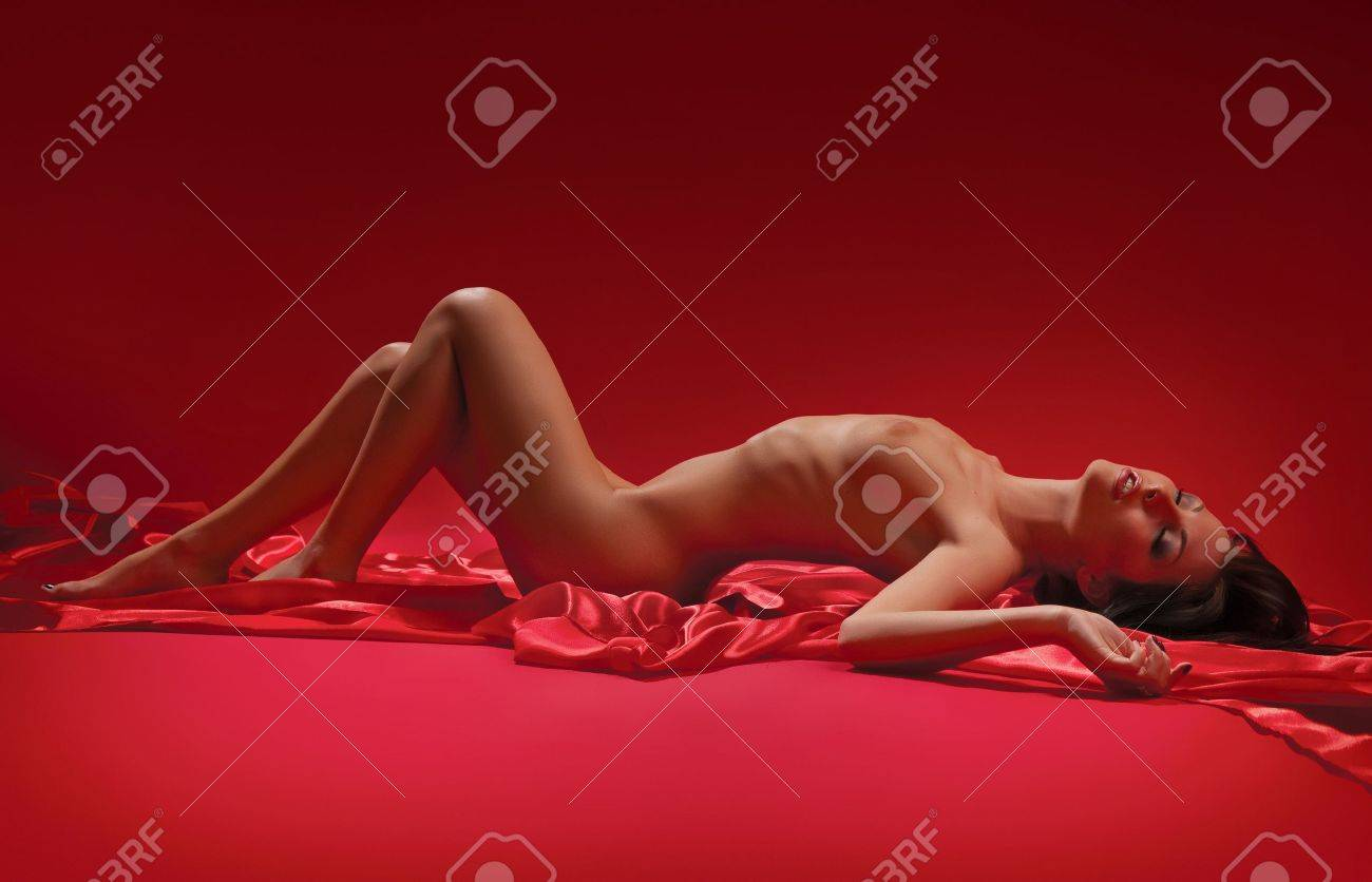 sensual naked brunette woman lying on a red background Stock Photo - 10952109