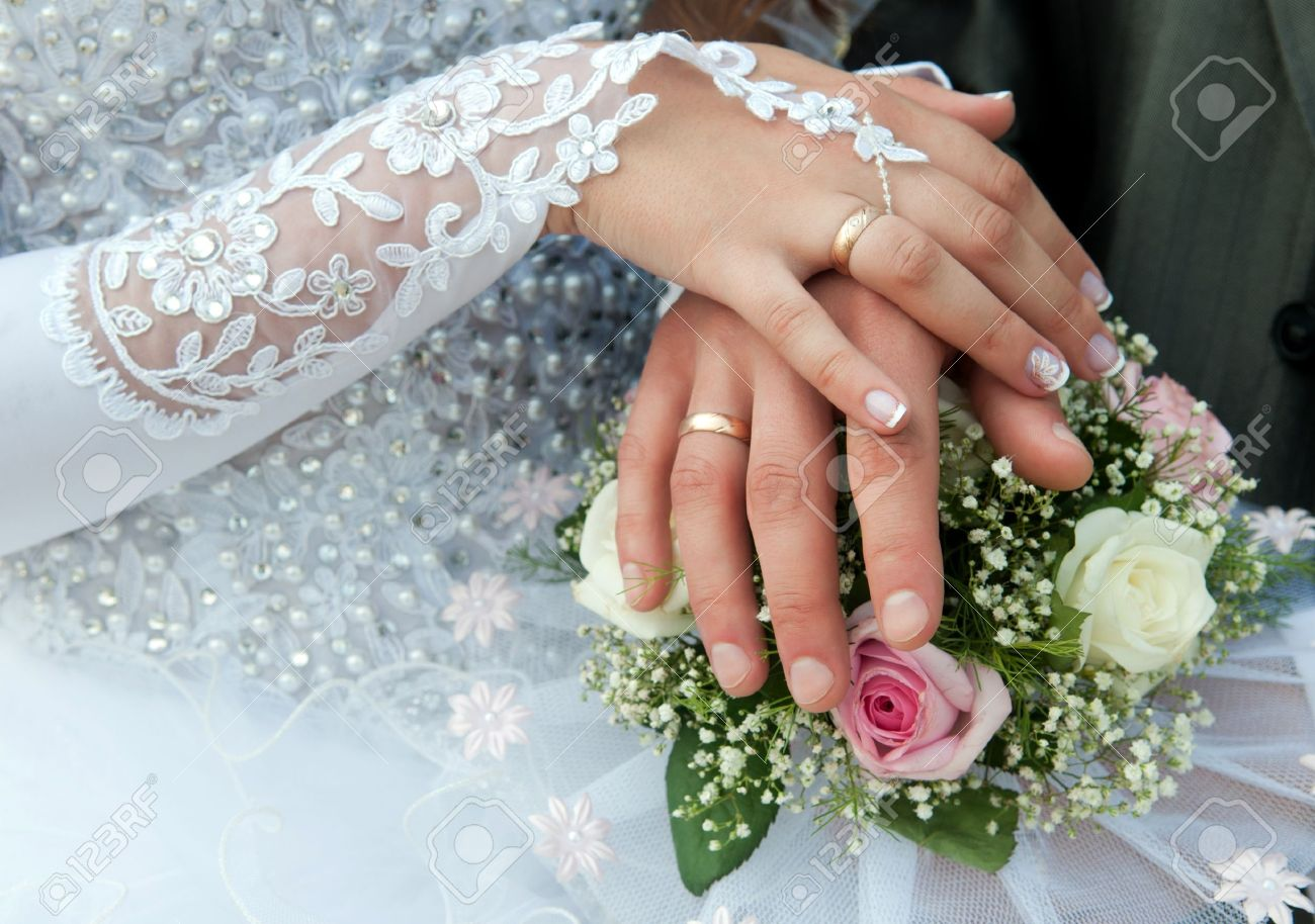 Hands Of Groom And Bride With Wedding Rings On Top Of The Brides