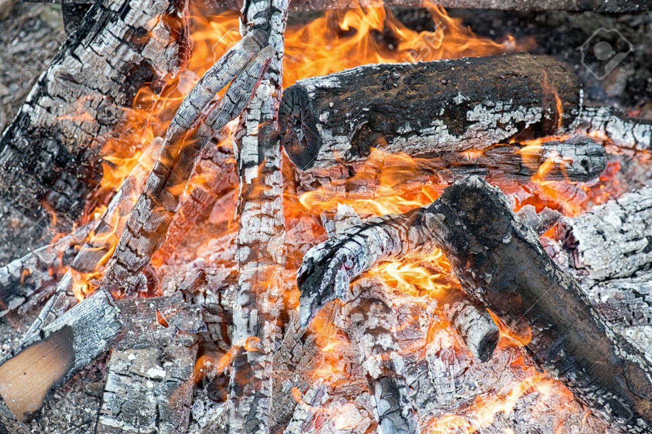 closeup of warm glowing embers in fireplace white and gray ash