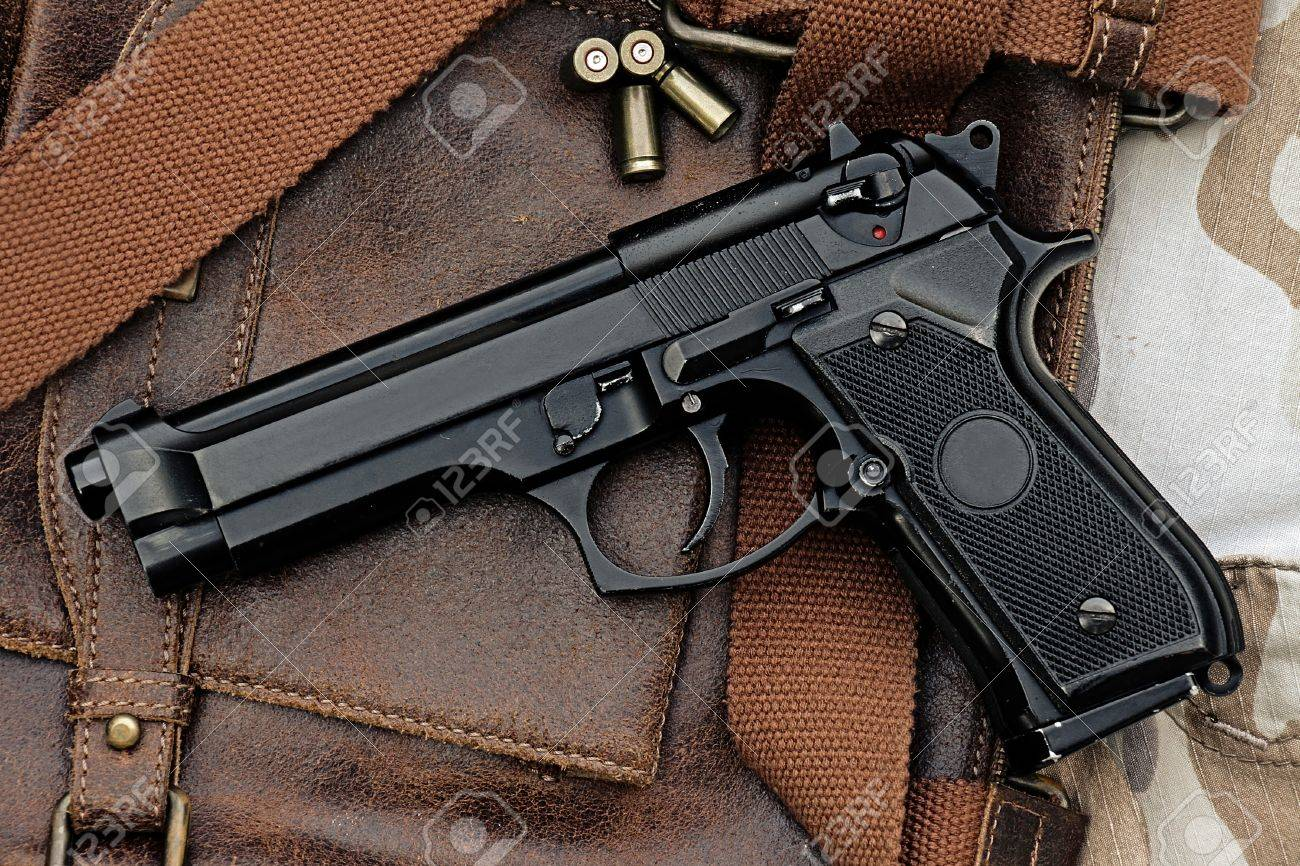 Semi-automatic handgun lying over a Leather handbag, 9mm pistol,