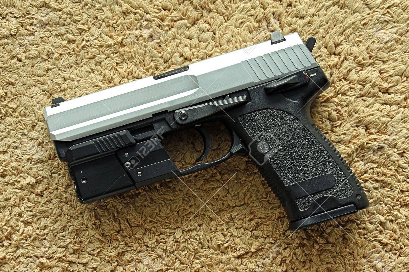 Semi-automatic handgun on carpet background, 9mm pistol