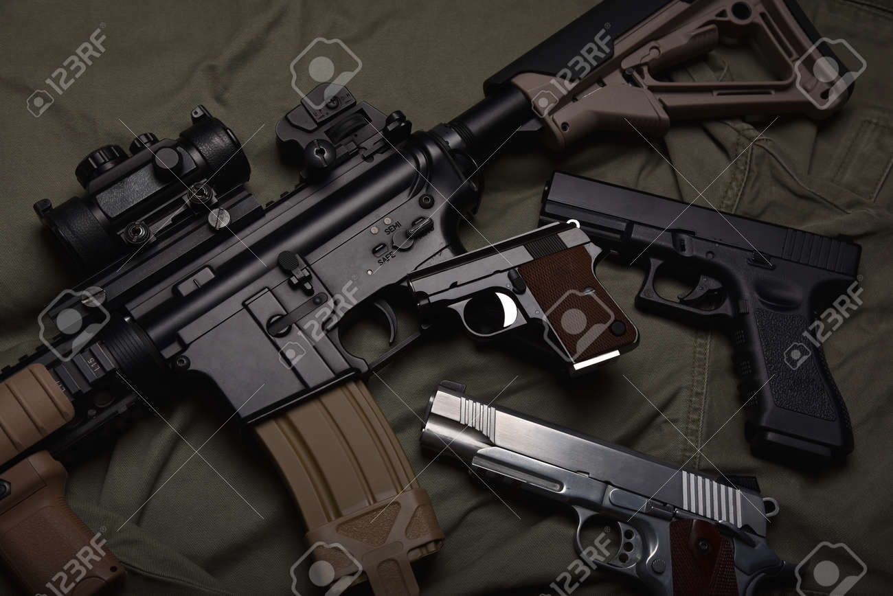 Weapons and military equipment for army, Assault rifle gun (M4A1) and pistol on green military uniform background. - 167100378