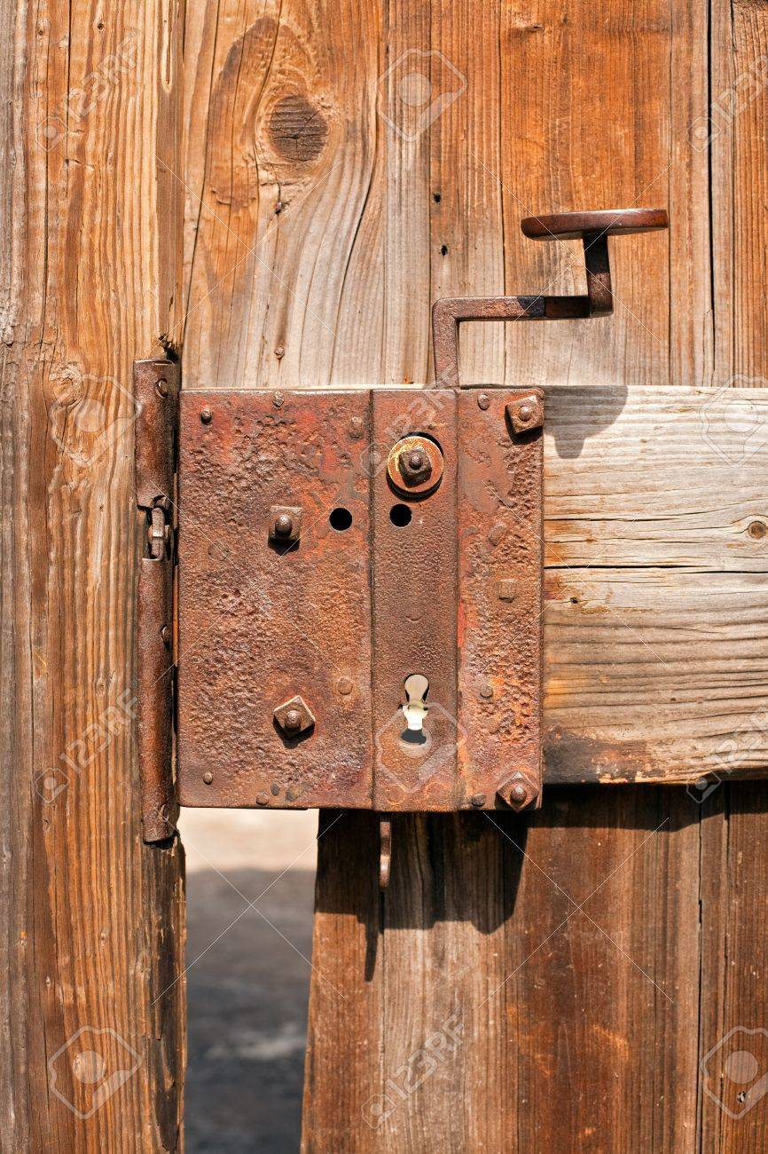 old rusty door lock on an ailing wooden gate Stock Photo - 5847776