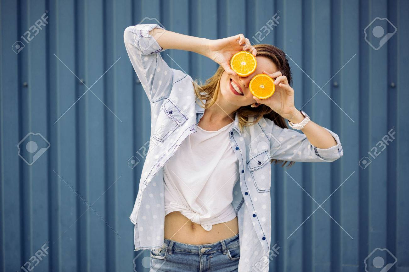 Smiling woman holding two grapefruits in hands on a blue background - 50201305