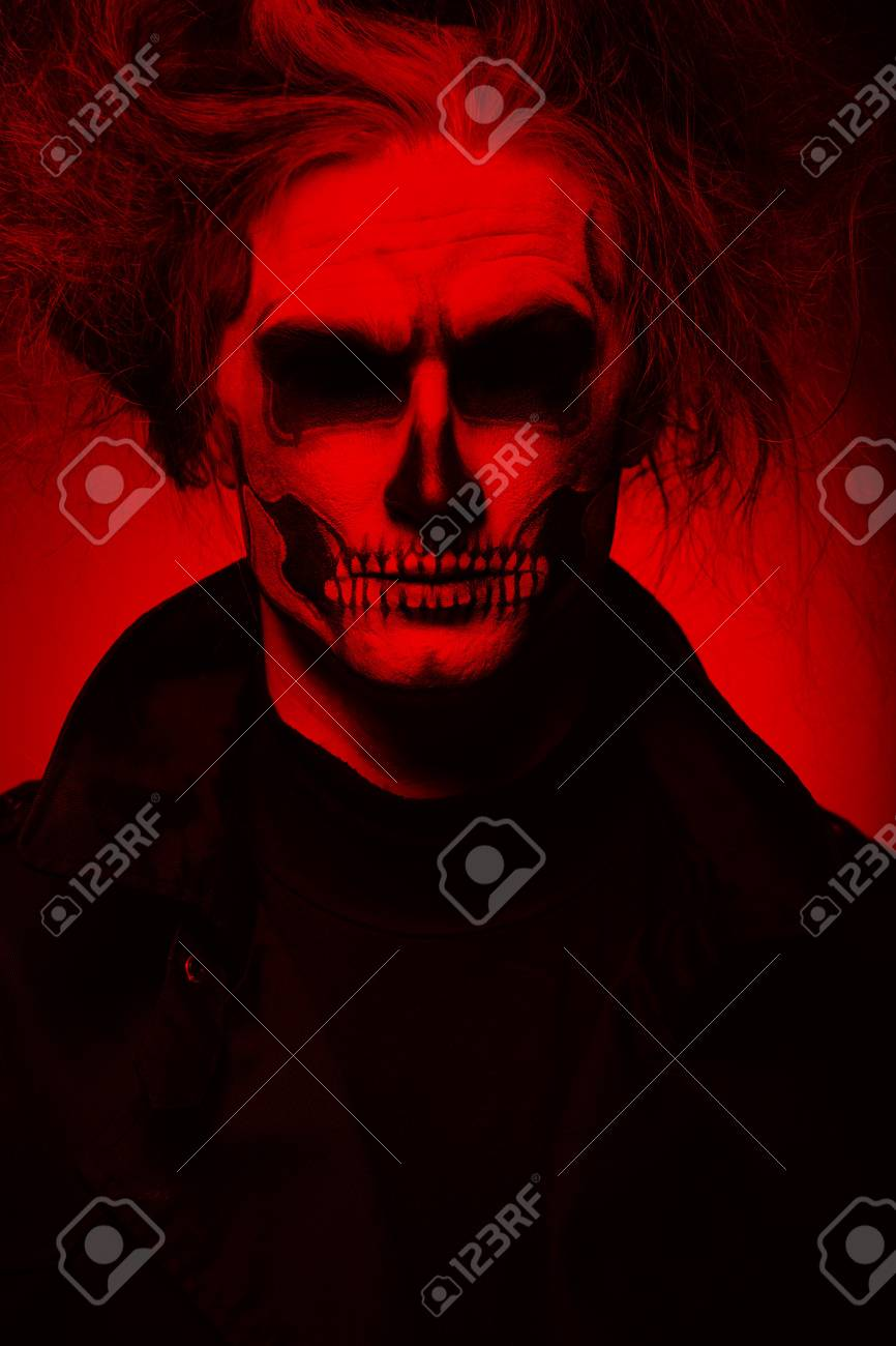 Portrait man with halloween skull makeup halloween or horror theme red filter stock photo