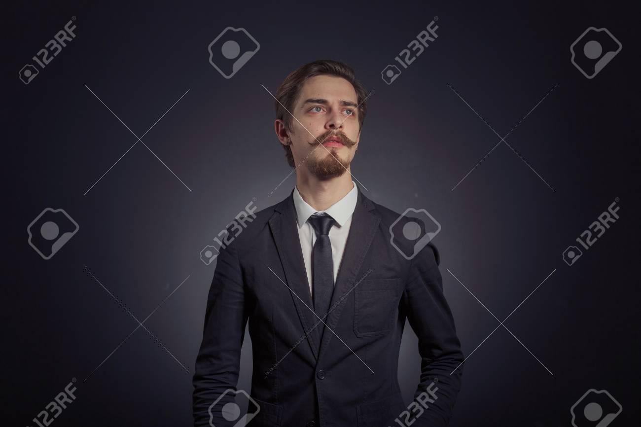 18230281fa Uomo d'affari elegante barbuto bello in vestito nero elegante che propone  nello studio su priorità bassa nera, lo spazio della copia