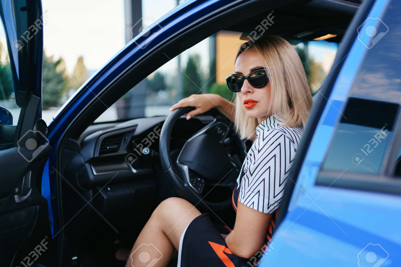 Confident and beautiful woman in sunglasses. Rear view of attractive young female in casual wear driving a car - 158991732