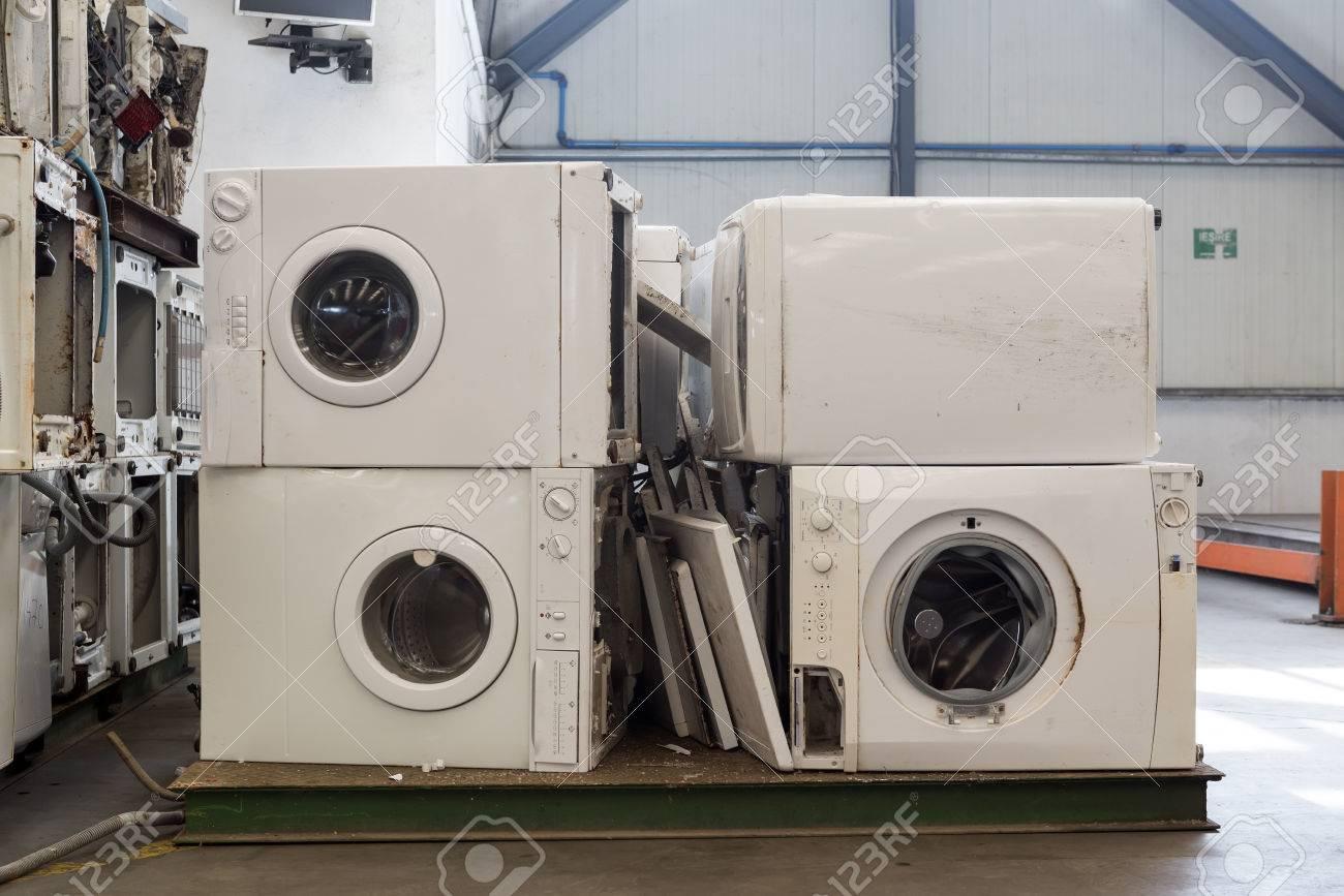 Stapel von gebrauchten und weggeworfenen waschmaschinen warten