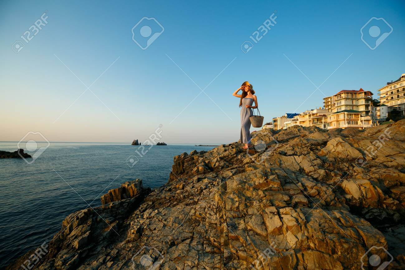 6176473fc191 Pretty woman with summer beach dress on stands on a rock beach and enjoys  sun on
