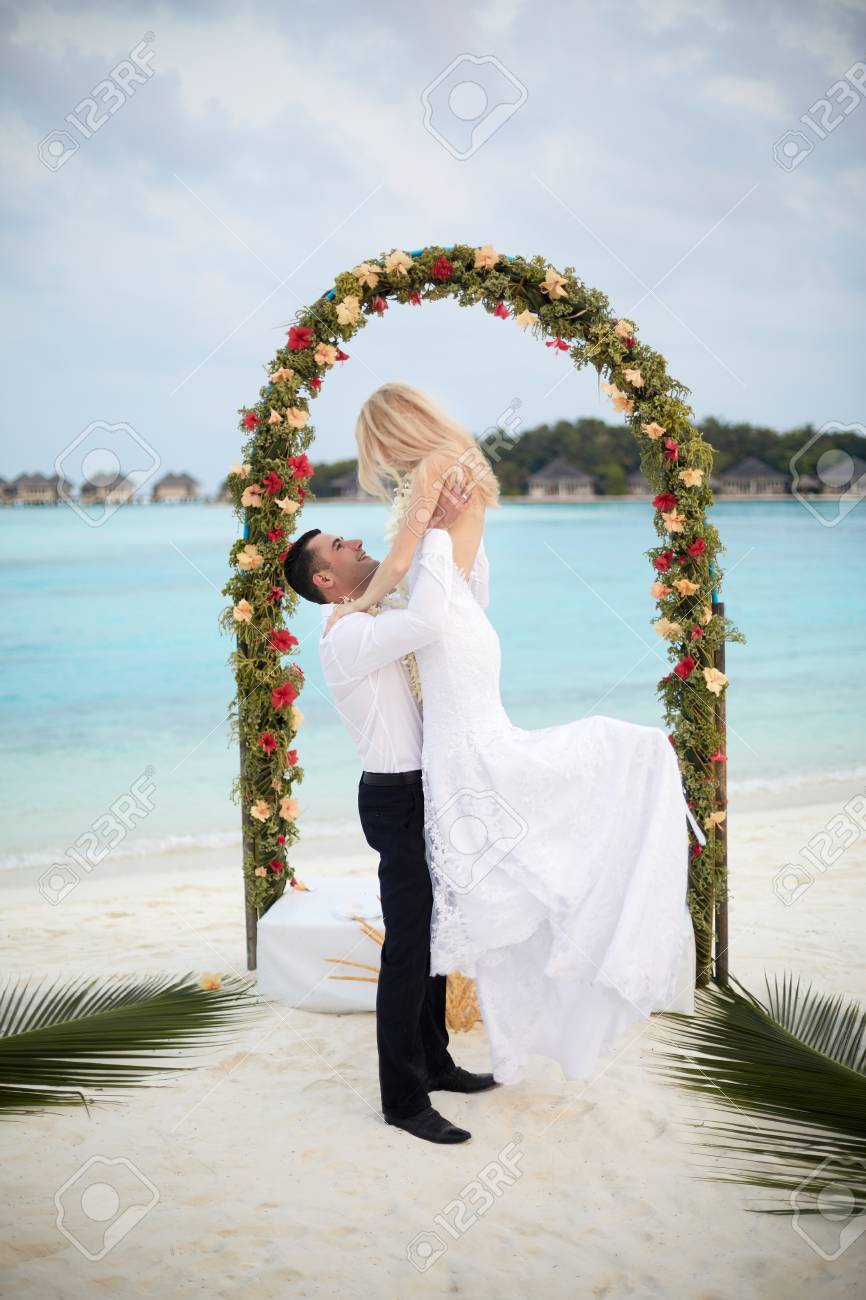 Happy Groom Holds Bride On His Hands Under Wedding Ceremony Arch On