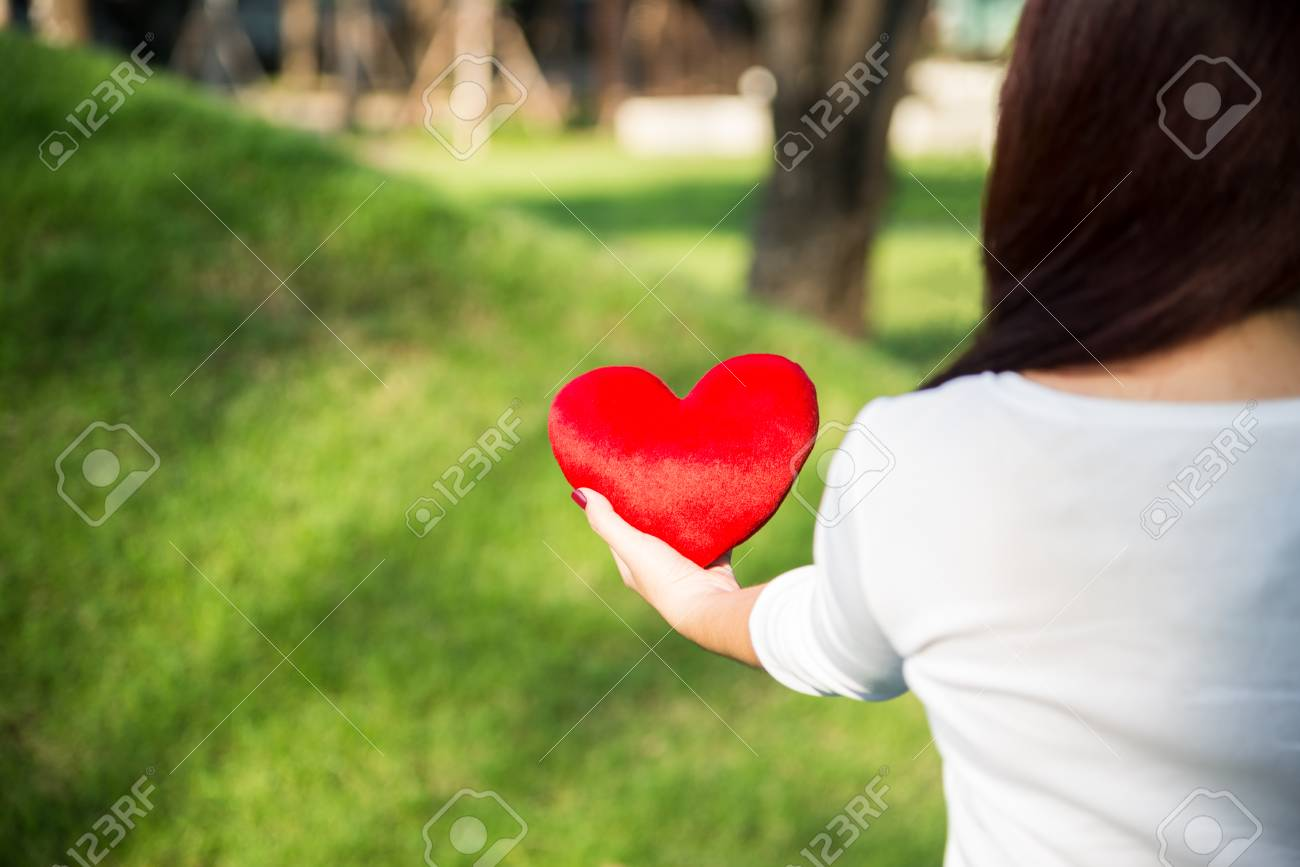 Asian Woman Holding Red Soft Heart Pillow With Left Hand At Park ...
