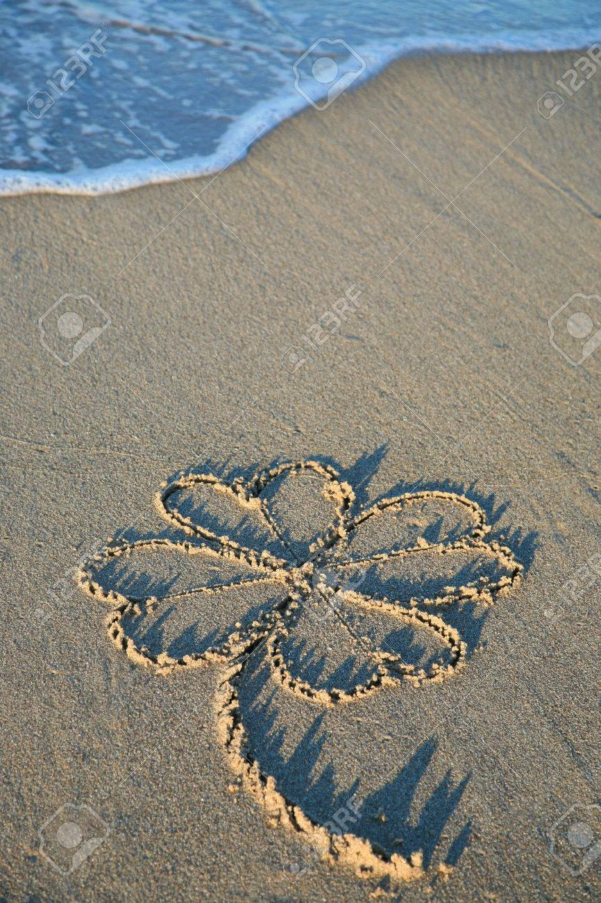four leaf clover painting in sand on the beach stock photo